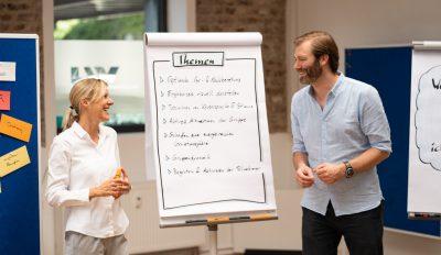 Moderationstraining für Scrum Master – die Trainer Alexandra Klingor und Alexander Kylburg gut gelaunt vor einem Themen-Flipchart