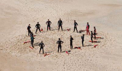 Übungsgruppe von Surfern steht am Strand im Kreis