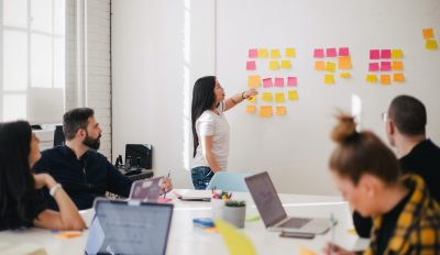 Retrospektive – Frau steht vor Team an Post-It-Wand